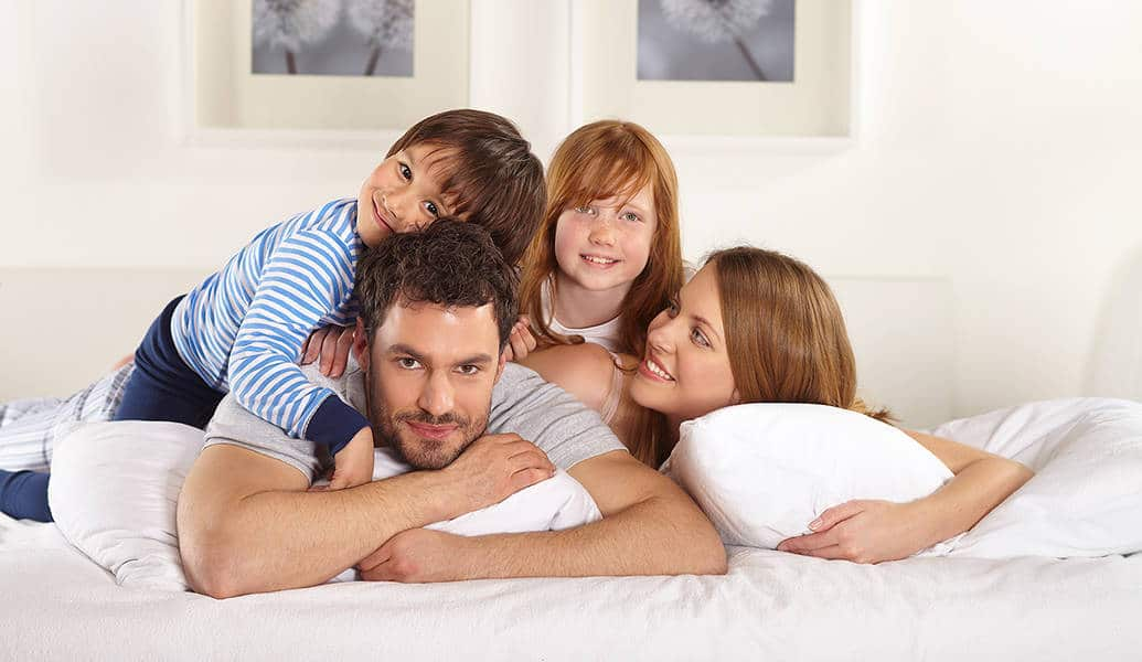 A family with beautiful smiles and healthy teeth cuddle in bed while posing for a photo.